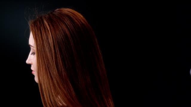 Beautiful redhead girl tossing her long hair