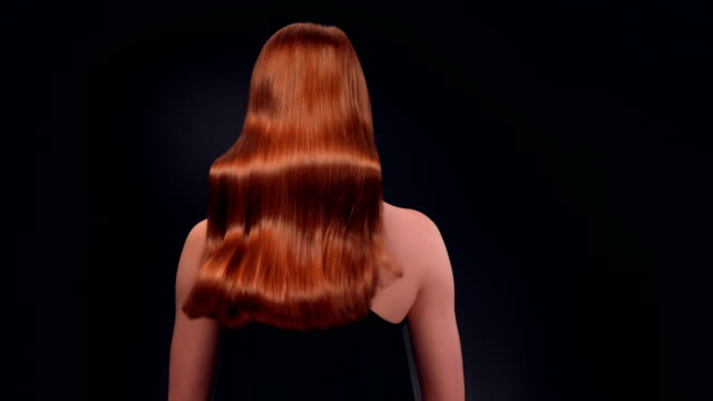 beautiful redhead woman tossing her long hair - shampoo per capelli video stock e b–roll