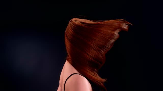 Beautiful redhead woman tossing long hair