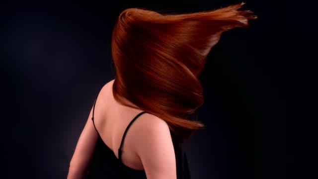 美しい赤毛の女性が長い髪を投げ