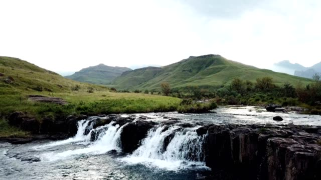 beautiful river flowing over a small waterfall - flowing stock videos & royalty-free footage