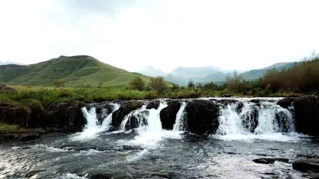 vídeos y material grabado en eventos de stock de hermoso río que fluye sobre una pequeña cascada - kwazulu natal