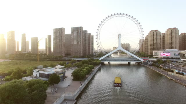 beautiful river through modern buildings and ferris wheel