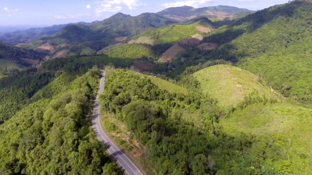 Beautiful Rural Road pass through Mountain with Green Forest
