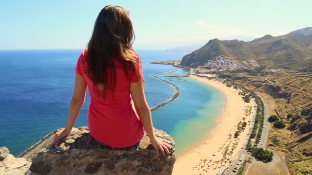 Beautiful Russian girl sitting and contemplating the Tenerife island from viewpoint with nice beach during travel vacations with warm and sunny days.