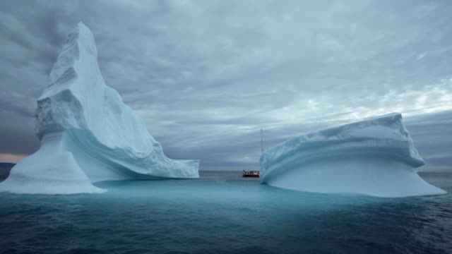 beautiful sailboat visible between the peaks of a tall white iceberg in grey water at dusk - disko bay, greenland - mountain peak stock videos & royalty-free footage