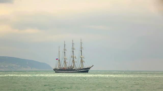 Beautiful sailing ship on a background of the coast