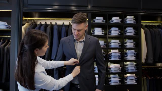 schöne verkäuferin hilft einem geschäftsmann versuchen, einen blazer in einem formellen kleid herrengeschäft - maßkonfektion stock-videos und b-roll-filmmaterial