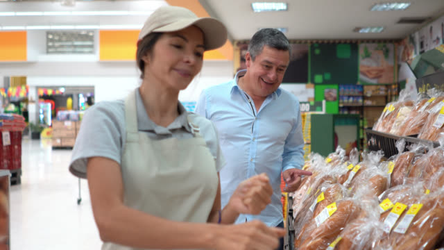 beautiful sales clerk suggesting a bread to male customer at the bakery section of the supermarket - customer stock videos & royalty-free footage