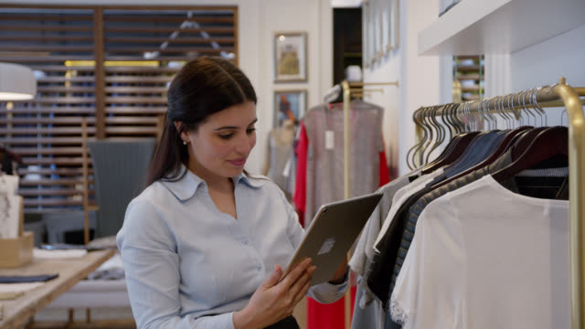 beautiful sales woman at a clothing store checking inventory holding a tablet - department store stock videos & royalty-free footage