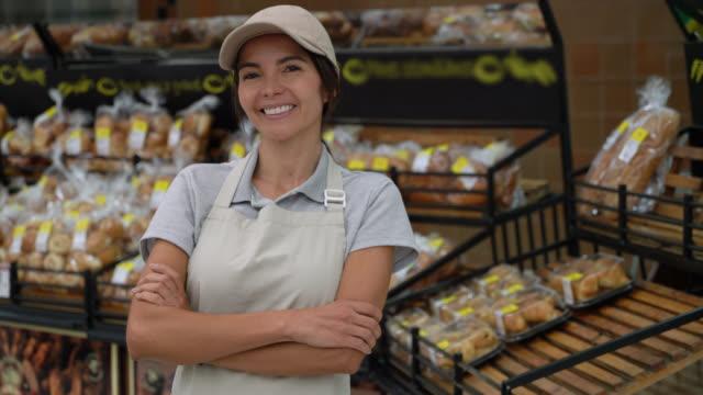 vídeos y material grabado en eventos de stock de hermosa mujer de ventas en la sección de panadería de supermercado frente a la cámara sonriendo con los brazos cruzados - supermercado