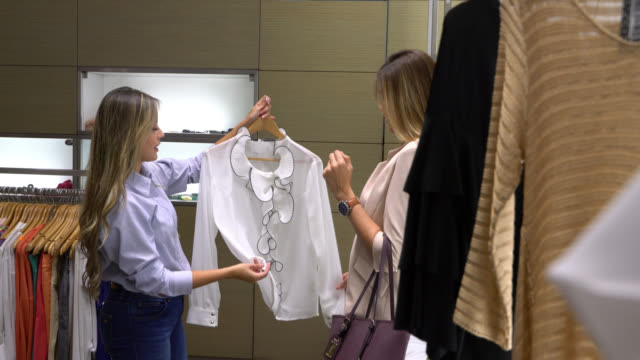 beautiful sales woman suggesting a blouse to female customer at a women's clothing store - assistant stock videos and b-roll footage