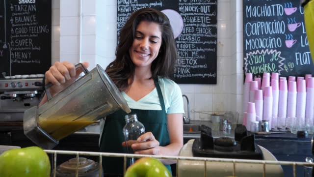 Beautiful saleswoman serving a juice in a bottle after using the blender