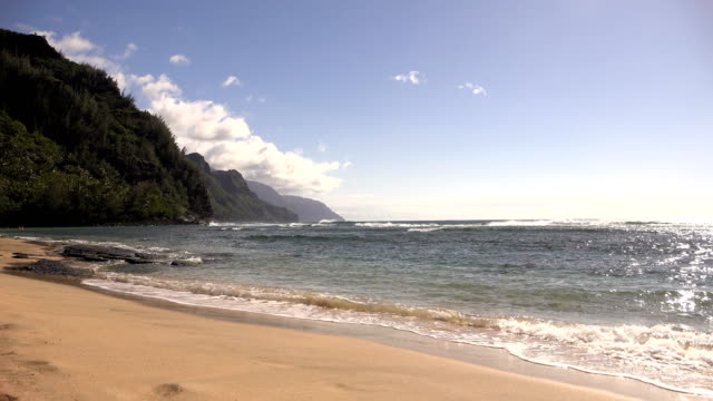 beautiful sandy beach on kauai island - butte rocky outcrop stock videos & royalty-free footage