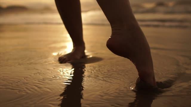 日没時に海のビーチを歩く女性の低いセクションの美しいシーン - 裸足点の映像素材/bロール