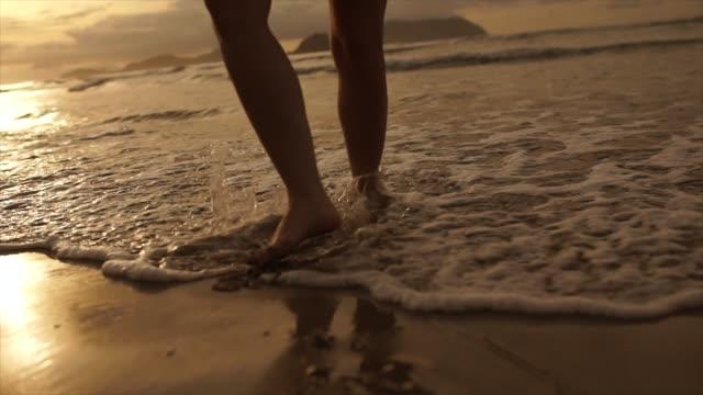 vídeos de stock, filmes e b-roll de bela cena de uma seção baixa de mulher andando na praia do oceano ao pôr do sol - star shape