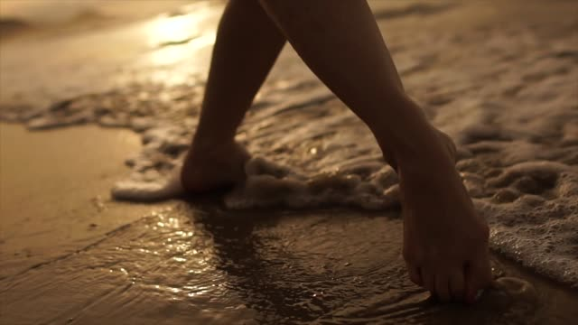 beautiful scene of a low section of woman walking on ocean beach at sunset - human leg stock videos & royalty-free footage