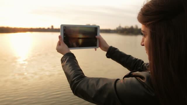 vídeos de stock e filmes b-roll de bela cena com um jovem adulto usando tablet digital. - sentar se