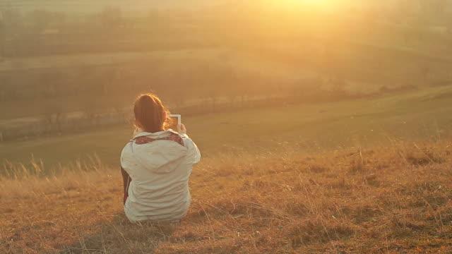 Bella scena con una giovane donna utilizzando una tavoletta digitale in natura.