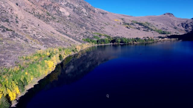 beautiful scenic of a lake in the wilderness with fishermen fishing in the morning sun. - mammoth lakes video stock e b–roll