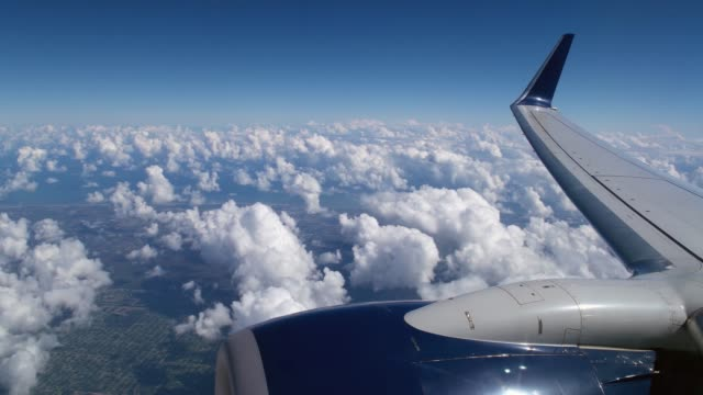 beautiful scenic view of blue sky and clouds with wing and engine in the foreground and includes ambient cabin sounds of passengers and air rushing by - aircraft wing stock videos & royalty-free footage