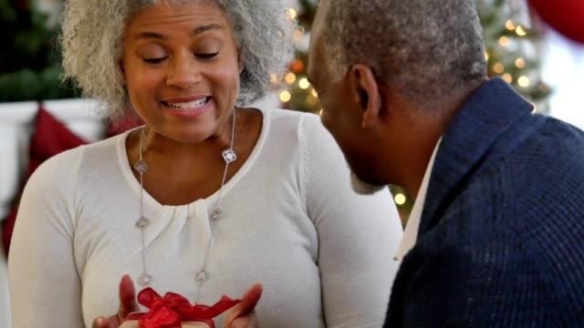 vídeos de stock, filmes e b-roll de linda mulher afro-americana sênior está animada para receber o presente de natal do marido - cara a cara