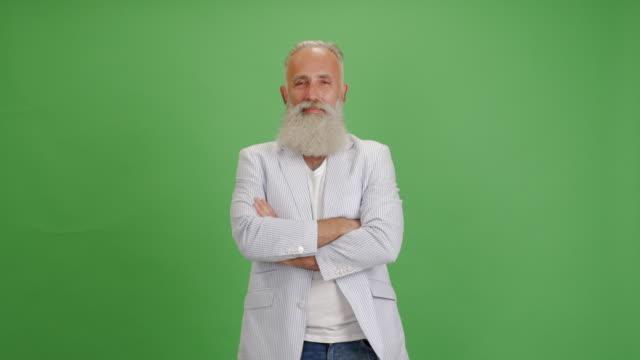 vacker äldre skäggig man ser på kameran, leende, armar korsade på en grön bakgrund - 50 59 years bildbanksvideor och videomaterial från bakom kulisserna