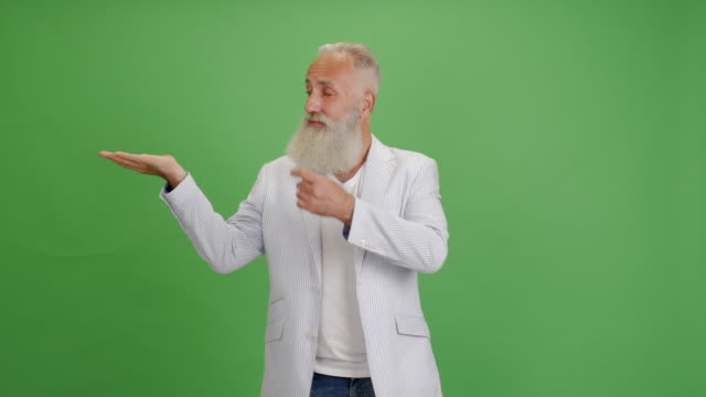 vacker äldre skäggig man visar kopia utrymme och visar tummen på en grön bakgrund - 50 59 years bildbanksvideor och videomaterial från bakom kulisserna