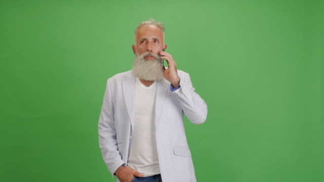 beautiful senior bearded man speaks on the smartphone on a green background - solid stock videos & royalty-free footage