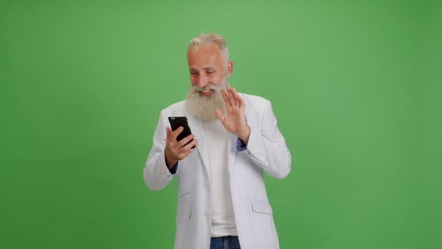 vacker äldre skäggig man talar på video kommunikation på en smartphone på en grön bakgrund - 50 59 years bildbanksvideor och videomaterial från bakom kulisserna