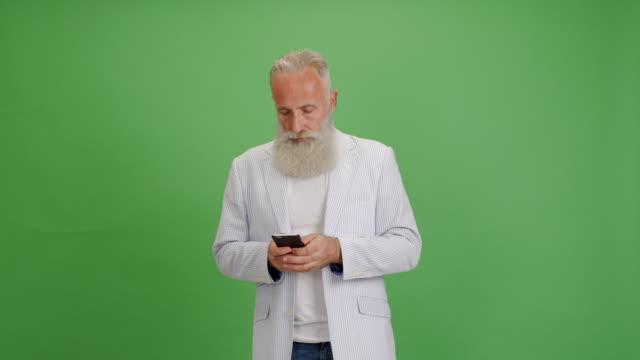 vacker äldre skäggig man använder en smartphone för meddelande på en grön bakgrund - 50 59 years bildbanksvideor och videomaterial från bakom kulisserna