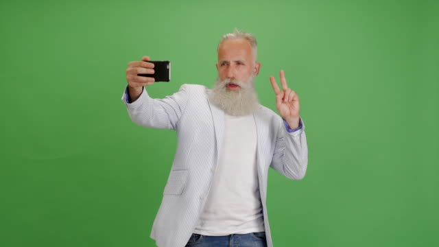 Beautiful senior bearded man uses a smartphone for selfie on a green background