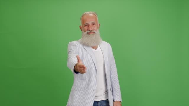 vacker äldre skäggig man med ett leende förlänger en hand för ett handslag på en grön bakgrund - 50 59 years bildbanksvideor och videomaterial från bakom kulisserna
