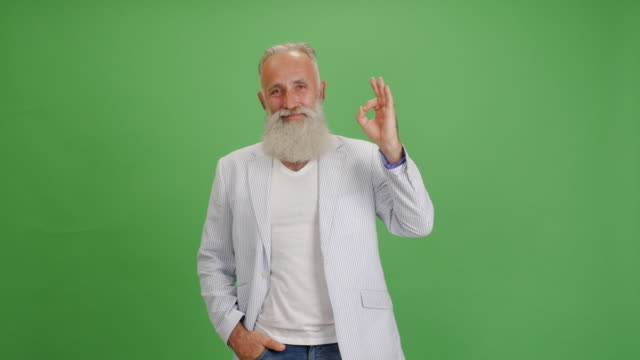 beautiful senior bearded man with a smile shows okay and thumbs up on a green background - thumbs up stock videos & royalty-free footage