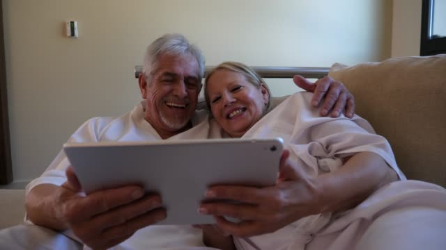 Beautiful senior couple lying down on the couch looking at photos on a digital tablet talking, laughing and smiling very happy