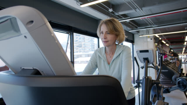 beautiful senior woman at the gym exercising on treadmill - cross trainer stock videos & royalty-free footage