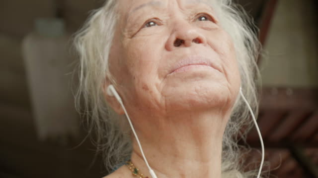 a beautiful senior woman listening to music with headphones and daydreams dancing to the music. concept: podcast, portrait, dancer and music - mp3 player stock videos & royalty-free footage
