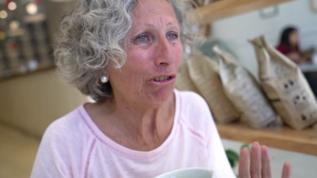 beautiful senior woman on a date talking and drinking coffee at a bakery - cafeteria stock videos & royalty-free footage
