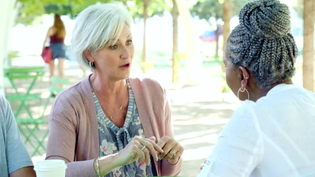 Beautiful senior woman talks with female friend over coffee