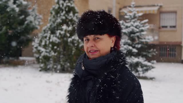 beautiful senior woman wearing winter hat and spending time outdoors while it's snowing - winter coat stock videos & royalty-free footage