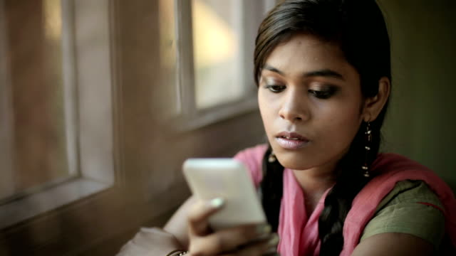 Beautiful serene Indian girl reading SMS sitting near window.