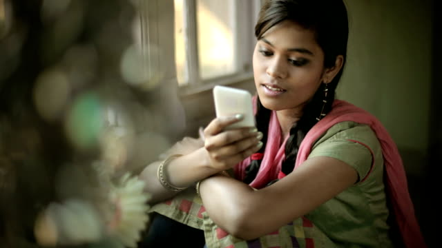 beautiful serene indian girl reading sms sitting near window. - indian ethnicity stock videos & royalty-free footage