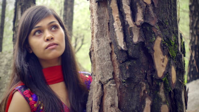 beautiful serene young woman standing with tree trunk. - solitude stock videos and b-roll footage