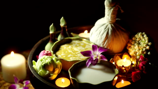 Beautiful set of herbal treatments and herbal ball for massage and spa decorated with Frangipani and lighting candles.
