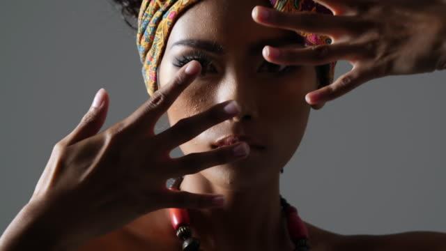 vidéos et rushes de belle sexy black woman en regardant la caméra, le jeune mannequin beau style africain traditionnel avec foulard, boucles d'oreilles et le maquillage sur fond sombre. portrait du côté vue du modèle de peau sombre sur un fond noir dans les coulisses. p - coiffure afro
