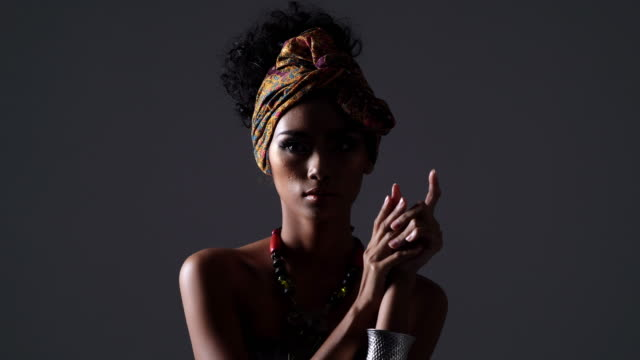vídeos de stock e filmes b-roll de beautiful sexy black woman,young beautiful fashion model with traditional african style with scarf, earrings and makeup on dark background.side view portrait of dark skinned model on a black backstage. light and shadow portrait - afro americano