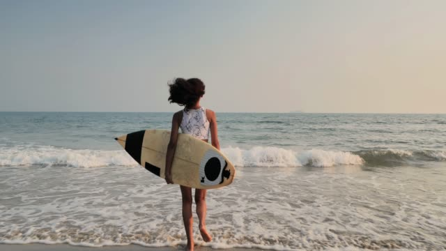 beautiful sexy surfer girl on the beach at sunset.sports cinemagraphs - teenage girls stock videos & royalty-free footage