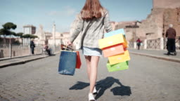 Beautiful shopaholic girl walking in Milan center with shopping bags full of purchases. Big sales in shopping mall, happiness and joy. Pretty woman dancing in Milan center with colorful shopping bags
