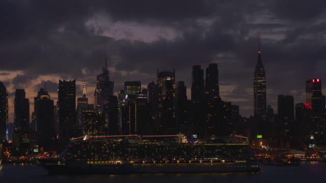 Beautiful shot of a lit up cruise ship going along the Hudson River against the lit up Midtown Manhattan Skyline