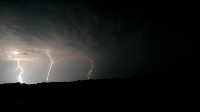 slo mo beautiful shot of lightning in the countryside - temporale video stock e b–roll